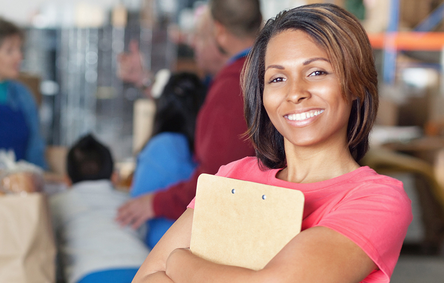 A beautiful mid adult woman holds a clipboard behind crossed arms as she stands in the middle of a bustling food bank and smiles for the camera. She is managing a food drive.