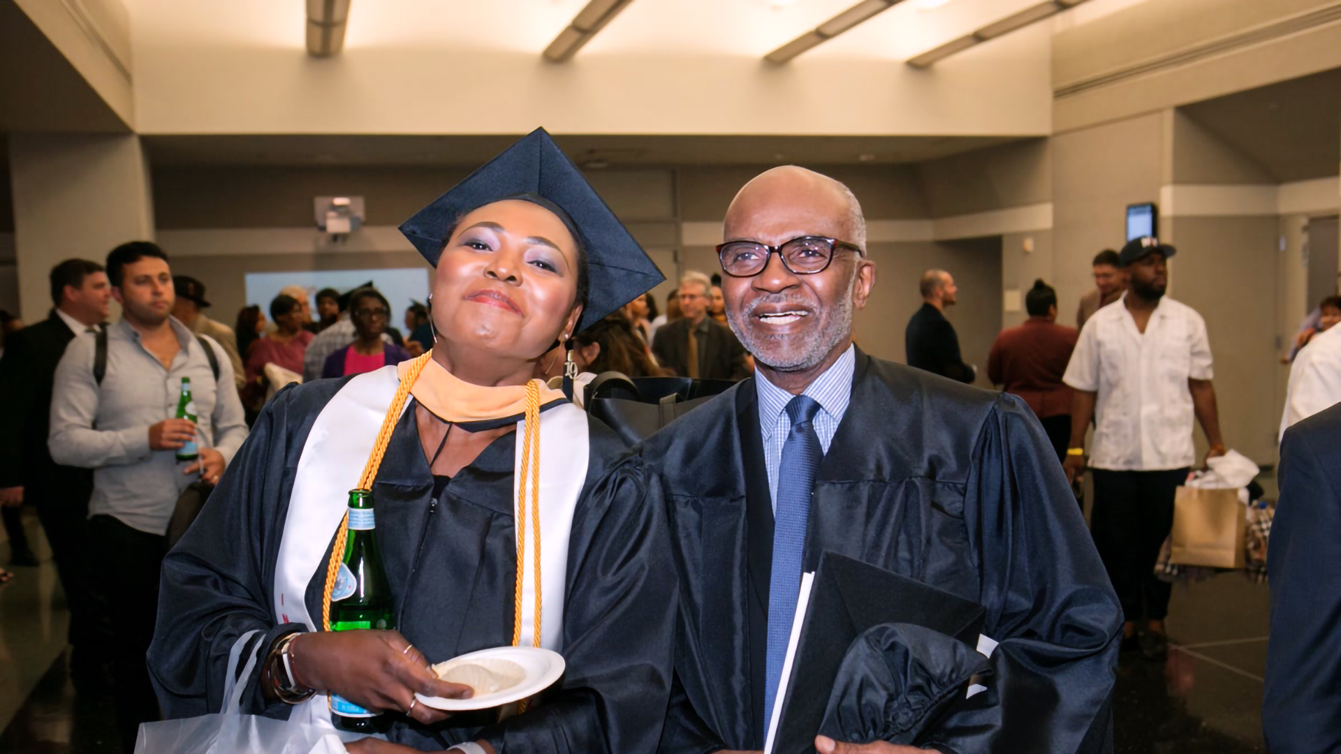 Distinguished Lecturer Dr. James Steele poses with student at SLU's 2019 commencement